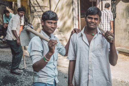 MUMBAI, INDIA - 08 JANUARY 2015: Two young Indian workers stand in street with hoe's in hands. Young boys and girls work as cheap labor throughout India. 에디토리얼