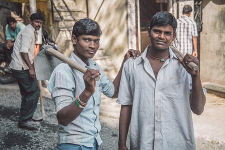 Mumbai, India - 08 enero de 2015: Dos trabajadores indios jóvenes de pie en la calle con la azada en la mano. chicos y chicas jóvenes trabajan como mano de obra en toda la India.