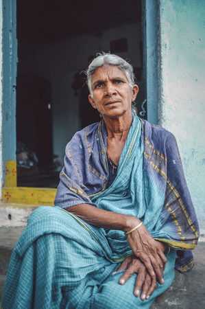 nosering: HAMPI, INDIA - 31 JANUARY 2015: Elderly Indian woman sits in sari in-front of home. Post-processed with grain, texture and colour effect.