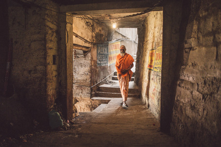ascetic: VARANASI, INDIA - 20 FEBRUARY 2015: A sadhu walks through a passage.  In Hinduism, a sadhu is a religious ascetic or holy person. Post-processed with grain, texture and colour effect.