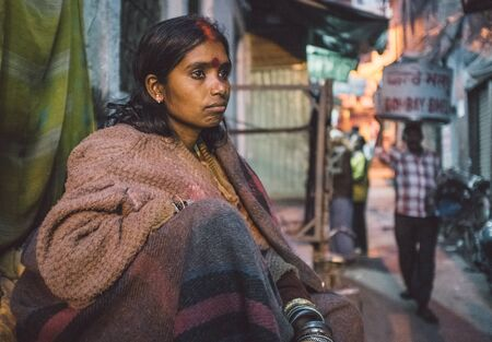 bindi: VARANASI, INDIA - 25 FEBRUARY 2015: Indian homeless woman sitting in street. Post-processed with grain, texture and colour effect. Editorial