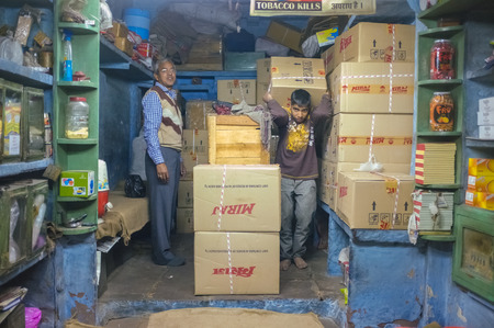 storeroom: JODHPUR, INDIA - 07 FEBRUARY 2015: Shop owner and young worker in storeroom of tobacco shop with Miraj chewing tobacco in boxes. Miraj produces the finest quality chewing tobacco.