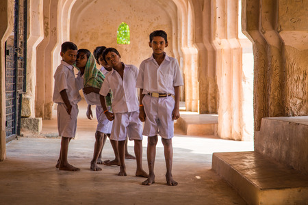 schoolboys: HAMPI, INDIA - 30 JANUARY 2015: Five schoolboys stand inside Queenss bath ruins. It is a colossal bath that exemplifies the architectural excellence prevalent during the days of the Vijayanagara Empire.