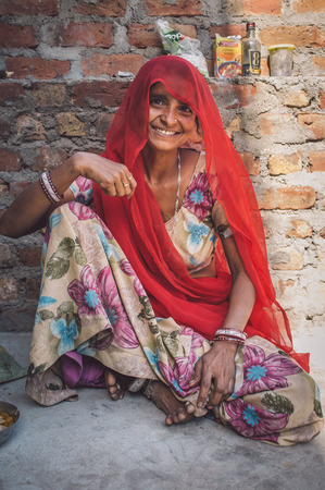 nosering: GODWAR REGION, INDIA - 13 FEBRUARY 2015: Indian woman in sari sits next to brick wall. Post-processed with grain, texture and colour effect. Editorial