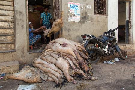 sheep skin: MUMBAI, INDIA - 12 JANUARY 2015: Dharavi slum butcher throws and piles raw sheep skin on street next to parked motorbike.