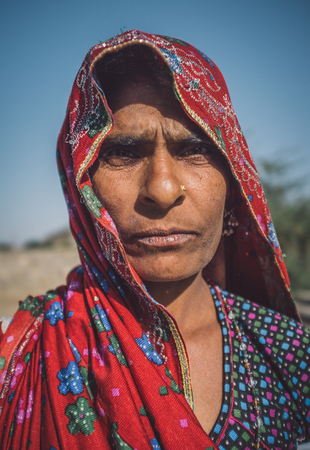 nosering: GODWAR REGION, INDIA - 14 FEBRUARY 2015: Rabari tribeswoman stands in field wearing saree. Post-processed with grain, texture and colour effect. Editorial