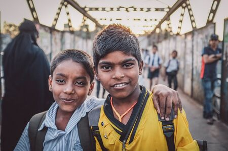 poor children: MUMBAI, INDIA - 12 JANUARY 2015: Indian school boys on bridge in Dharavi slum. Post-processed with grain, texture and colour effect.