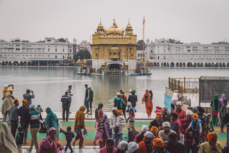 harmandir sahib: AMRITSAR, INDIA - 01 MARCH 2015: Pilgrims at the Golden Temple, the holiest Sikh gurdwara in the world. Post-processed with texture and grain. Editorial
