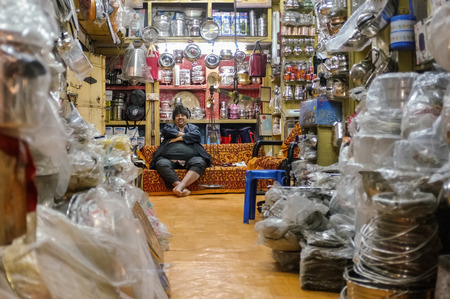 closing time: JODHPUR, INDIA - 07 FEBRUARY 2015: Shop owner with hat sitting on couch and resting before closing time. Stores with kitchen pottery and other products made from metal are common on Asian markets.