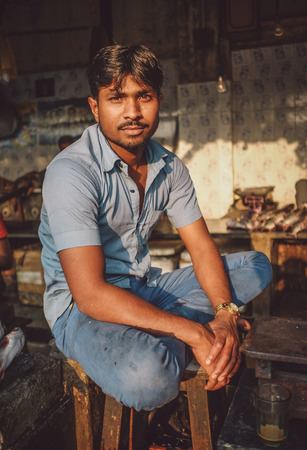 dhobi ghat: MUMBAI, INDIA - 08 JANUARY 2015: Worker on a fishmarket next to Dhobi ghat poses while waiting for customers. Post-processed with grain, texture and colour effect..