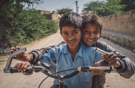 hait: GODWAR REGION, INDIA - 15 FEBRUARY 2015: Two boys on a bicycle in empty village street. Post-processed with grain, texture and colour effect.