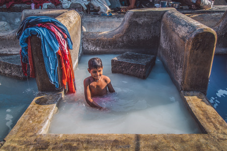 laundromat: MUMBAI, INDIA - 10 JANUARY 2015: Indian child bathes in traditional laundromat pool in Dhobi Ghat. Post-processed with grain, texture and colour effect.