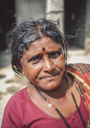 bindi: HAMPI, INDIA - 01 FEBRUARY 2015: Indian middle-aged woman with bindi on street in-front of home. Post-processed with grain, texture and colour effect.