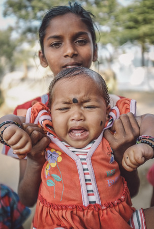 cries: HAMPI, INDIA - 31 JANUARY 2015: Indian baby with bindi cries while being held by family member. Post-processed with grain, texture and colour effect. Editorial