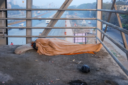 the whole body: MUMBAI, INDIA - 05 FEBRUARY 2015: Person sleeps on overpass on dirty ground with whole body covered under blanket. Common scene on Indias streets.