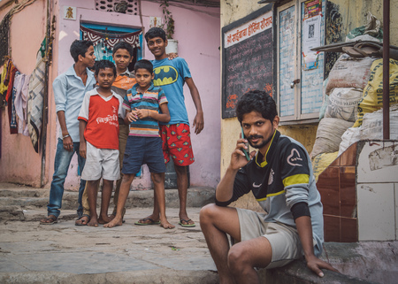 conversaciones: MUMBAI, INDIA - 16 JANUARY 2015: Five boys stand together in slum street while older boy talks on cellphone. Editorial