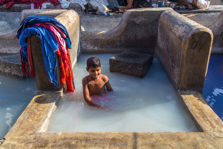 dhobi ghat: MUMBAI, INDIA - 10 JANUARY 2015: Indian child bathes in traditional laundromat pool in Dhobi Ghat. A well known open air laundromat in Mumbai.