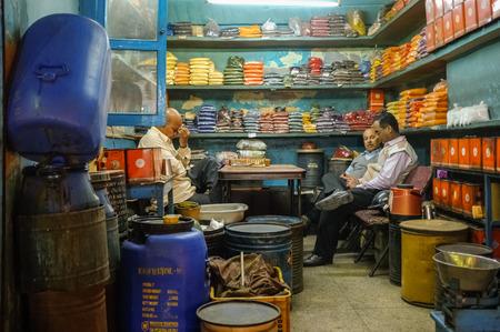 Jodhpur - 7. Februar 2015: Inhaber der Gewürzladen Massagen Stirn nach langen Arbeitstag, während Kunden zu diskutieren Geschäft. Lange Arbeitszeiten sind in Indien weit verbreitet.