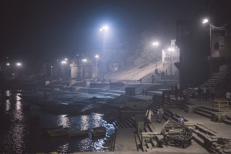 postproduction: VARANASI, INDIA - 20 FEBRUARY 2015: Night scene on Varanasi ghats with locals and boats. Post-processed with grain, texture and colour effect.