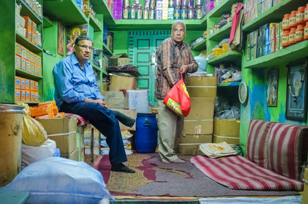 labourers: JODHPUR, INDIA - 07 FEBRUARY 2015: Shop owner waiting while customer looks for goods to buy. Apart from cheap labourers, shop owners also stay in stores until late working hours.