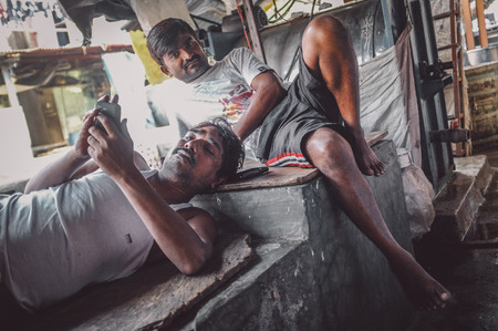 dhobi ghat: MUMBAI, INDIA - 08 JANUARY 2015: Indian workers take a rest after an early morning shift in Dhobi ghat. Post-processed with grain, texture and colour effect. Editorial