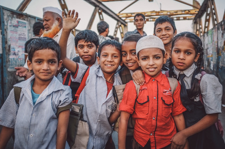 uniforms: MUMBAI, INDIA - 12 JANUARY 2015: Indian children after school in Dharavi slum. Post-processed with grain, texture and colour effect.