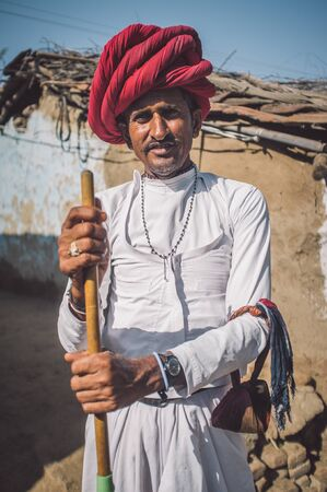 mud house: GODWAR REGION, INDIA - 13 FEBRUARY 2015: Rabari tribesman stands in courtyard of home wearing traditional clothes and holds herding stick. Post-processed with grain, texture and colour effect. Editorial