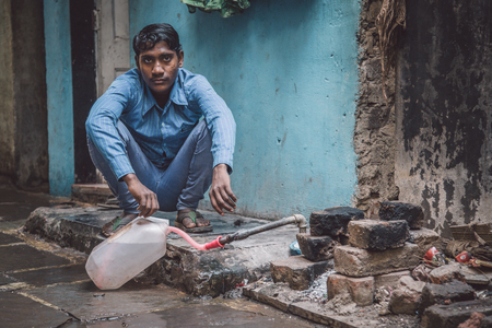 MUMBAI, INDIA - 12 JANUARY 2015: Young Indian man fills water tank in street. Dharavi slum mostly has drinkable water. Post-processed with grain, texture and colour effect.