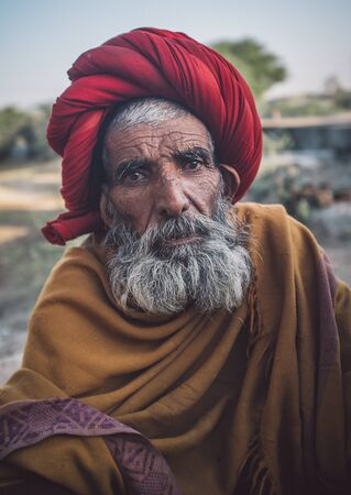 sholders: GODWAR REGION, INDIA - 14 FEBRUARY 2015: Elderly Rabari tribesman with red turban and blanket around the shoulders. Post-processed with grain, texture and colour effect.. Editorial