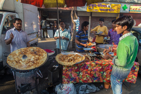 10 fingers: MUMBAI, INDIA - 10 JANUARY 2015: Street vendor makes Halwa poori close to Dhobi Ghat. A sweet bread and type of candy made for breakfast. Customers eat with fingers. Editorial