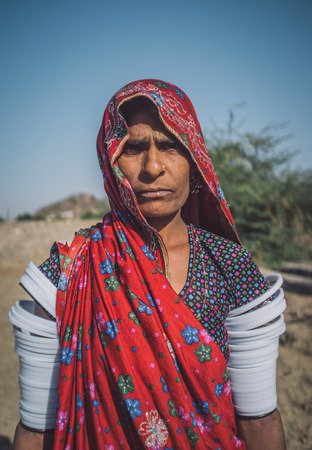 nosering: GODWAR REGION, INDIA - 14 FEBRUARY 2015: Rabari tribeswoman stands in field wearing saree and upper-arm bracelets. Post-processed with grain, texture and colour effect.
