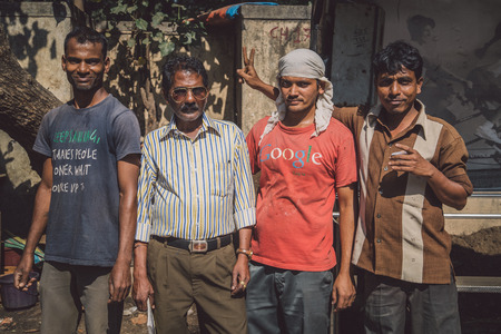 teases: MUMBAI, INDIA - 09 JANUARY 2015: Three Indian men stand with construction manager. One man teases manager. Post-processed with grain, texture and colour effect.