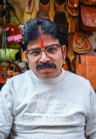 bindi: JODHPUR, INDIA - 07 FEBRUARY 2015: Store owner with mustache wearing glasses, gold earings and bindi sitting infront of shop. Rajasthan is known for leather designs than are sold around the country.