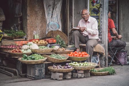 뭄바이, 인도 -17-1 월 17 일 : 노인 인도 사업가 시장 거리에서 식료품 점 앞의 고객을 기다립니다. 에디토리얼