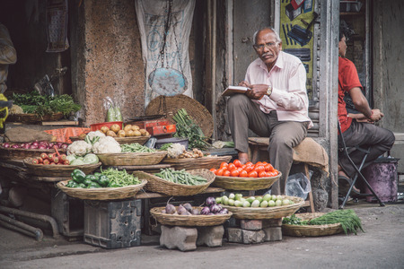 grocery baskets: MUMBAI, INDIA - 17 JANUARY 2015: Elderly Indian businessman waits for customers in front of grocery store in market street. Editorial
