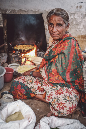 rural: KAMALAPURAM, INDIA - 02 FABRUARY 2015: Elderly Indian woman in traditional clothes fries vegatables. Post-processed with grain, texture and colour effect.