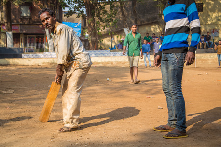 teammate: MUMBAI, INDIA - 16 JANUARY 2015: Adult Indian man holds wooden cricket bat and waits for ball while teammate, partly out of frame, stands next to him .