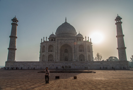 love dome: AGRA, INDIA - 28 FEBRUARY 2015: Backlit view of Taj Mahal from West side with tourist taking selfie.