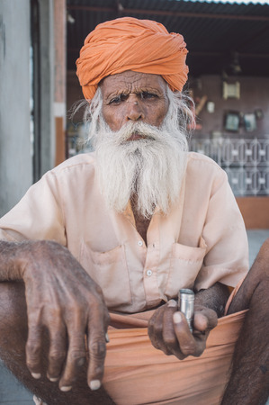sits: GODWAR, INDIA - 12 FEBRUARY 2015: Elderly Indian tribesman with turban in lungi sits on ground in front of temple. Editorial