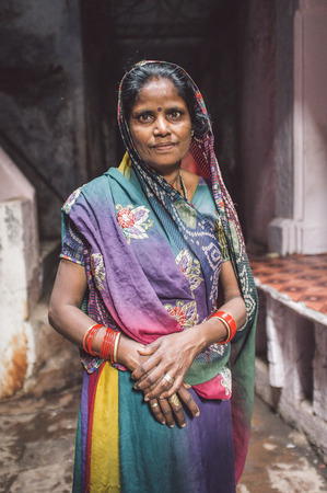 bindi: VARANASI, INDIA - 20 FEBRUARY 2015: Indian woman in colorful sari with bindi stands in street. Post-processed with grain, texture and colour effect.