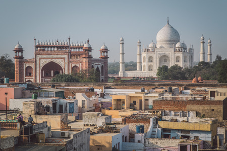 neighbouring: AGRA, INDIA - 27 FEBRUARY 2015: Taj Mahal, Great Gate and rooftops of neighbouring houses. Post-processed with grain, texture and colour effect. Editorial