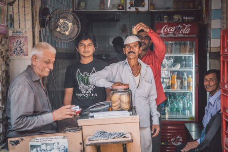 postproduction: MUMBAI, INDIA - 17 JANUARY 2015: Indian workers pause for photo and have fun. Post-processed with grain, texture and colour effect.