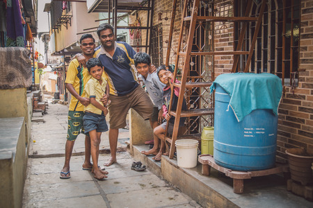 slum: MUMBAI, INDIA - 16 JANUARY 2015: Five family members stand together in slum street. Post-processed with grain, texture and colour effect.
