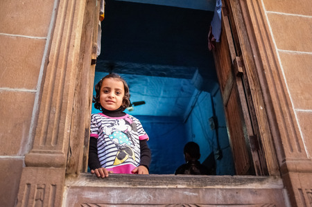 minnie mouse: JODHPUR, INDIA - 07 FEBRUARY 2015: Little girl in Minnie Mouse shirt looking through window in blue-painted room. Common scene of blue-painted walls inside and outside of homes in old part of Jodhpur.