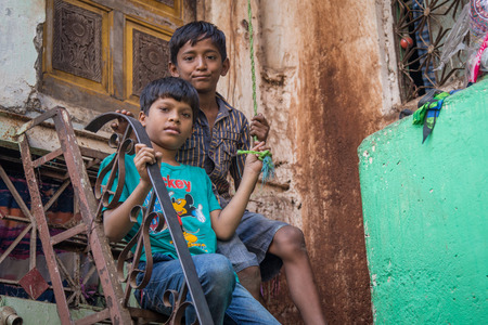 MUMBAI, INDIA - 12 JANUARY 2015: Two young boys sit on high stairs in front of home in Dharavi slum. Dharavi is one of the largest slums in the world.