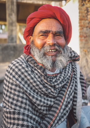 gujarat: GODWAR REGION, INDIA - 14 FEBRUARY 2015: Elderly Rabari tribesman with red turban and blanket around the shoulders. Post-processed with grain, texture and colour effect.