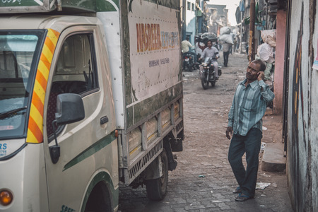 slums: MUMBAI, INDIA - 12 JANUARY 2015: Indian man stands next to truck in Dharavi slum and talks on cellphone. Dharavi is one of the largest slums in the world. Editorial