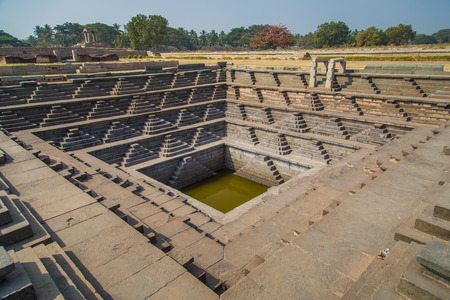 temple tank: Stepped tank and ruins of Hampi, India.