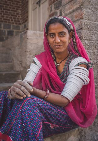 nosering: GODWAR REGION, INDIA - 15 FEBRUARY 2015: Indian tribeswoman sitting in front of home in saree decorated with upper-arm bracelets. Post-processed with grain, texture and colour effect.