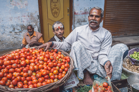 grocer: VARANASI, INDIA - 20 FEBRUARY 2015: Grocer puts tomatoes from basket into plastic bag for customer on street market.